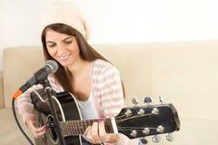 Muchacha que toca la guitarra y que canta en el micrófono Fotos de archivo libres de regalías