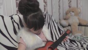 Muchacha que toca la guitarra y que se sienta detrás del oso de peluche metrajes