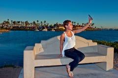 Muchacha que toma el selfie en el puerto deportivo Imágenes de archivo libres de regalías