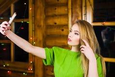 Muchacha que toma el selfie que lleva el vestido verde imagenes de archivo