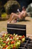 Muchacha que toma el sol del Shish-kebab vegetal de la barbacoa Fotografía de archivo libre de regalías