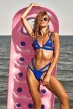 Muchacha que toma el sol en círculo inflable del rosa de la playa a disposición Imagen de archivo