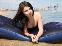 Muchacha que toma el sol en el colchón de aire en el mar Fotografía de archivo libre de regalías