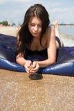 Muchacha que toma el sol en el colchón de aire en el mar Imágenes de archivo libres de regalías