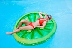Muchacha que toma el sol en inflable en piscina Imágenes de archivo libres de regalías