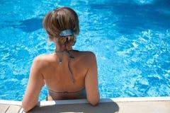 Muchacha que toma el sol por la piscina Imagen de archivo