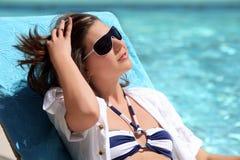 Muchacha que toma el sol por la piscina Imagenes de archivo