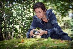 Muchacha que toma imágenes de la naturaleza en el bosque en la piedra grande con el musgo Foto de archivo libre de regalías