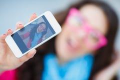 Muchacha que toma imágenes de sí mismo en su teléfono celular Fotos de archivo