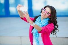 Muchacha que toma imágenes de sí mismo en su teléfono celular Imágenes de archivo libres de regalías