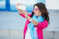Muchacha que toma imágenes de sí mismo en su teléfono celular Foto de archivo libre de regalías