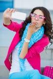 Muchacha que toma imágenes de sí mismo en su teléfono celular Foto de archivo