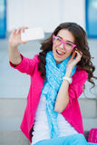 Muchacha que toma imágenes de sí mismo en su teléfono celular Imagen de archivo libre de regalías