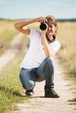 Muchacha que toma la foto con la cámara Imagen de archivo