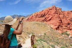 Muchacha que toma la foto con su smartphone en caminar viaje Fotos de archivo libres de regalías