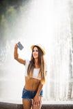 Muchacha que toma la foto del selfie cerca de la fuente Imagen de archivo libre de regalías