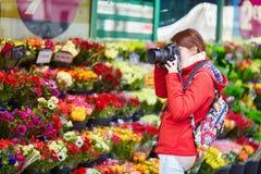Muchacha que toma la foto en una floristería parisiense Fotos de archivo libres de regalías