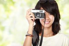 Muchacha que toma la imagen con la cámara del vintage Foto de archivo