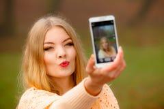Muchacha que toma la imagen del uno mismo con el teléfono al aire libre Fotografía de archivo libre de regalías