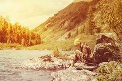 Muchacha que toma la imagen por el teléfono móvil en el lago en puesta del sol Fotos de archivo libres de regalías