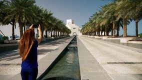 Muchacha que toma las fotos con smartphone en Doha cerca de las palmeras metrajes