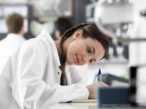 Muchacha que toma notas en clase de la ciencia Foto de archivo libre de regalías