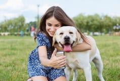 Muchacha que toma un selfie con su perro Fotos de archivo