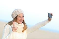 Muchacha que toma un selfie con su teléfono elegante en invierno Imágenes de archivo libres de regalías