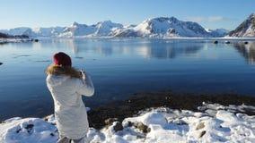 Muchacha que toma una foto del fiordo soleado del invierno en el archipiélago de Lofoten en la Noruega septentrional almacen de metraje de vídeo