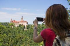 Muchacha que toma una imagen de un castillo hermoso en una colina Imagenes de archivo