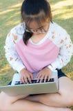 Muchacha que trabaja con el ordenador portátil en hierba Fotos de archivo libres de regalías