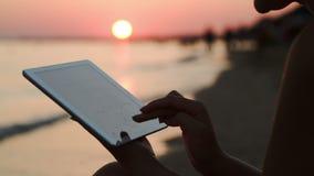 Muchacha que trabaja con la tableta en la playa en la puesta del sol