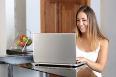 Muchacha que trabaja con un ordenador portátil en casa Fotos de archivo