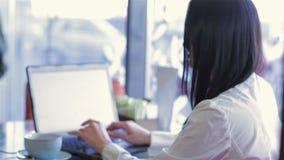 Muchacha que trabaja con un ordenador portátil en un café acogedor metrajes