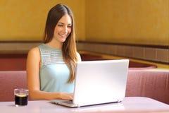 Muchacha que trabaja con un ordenador portátil en un restaurante Imágenes de archivo libres de regalías