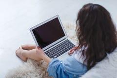 Muchacha que trabaja detrás del ordenador portátil cerca de cama en el fondo blanco Imagen de archivo