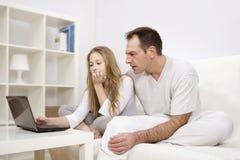 Muchacha que trabaja en el ordenador con su padre Imagen de archivo