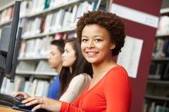 Muchacha que trabaja en el ordenador en biblioteca Imagen de archivo