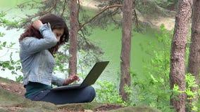 Muchacha que trabaja en el ordenador portátil al aire libre metrajes