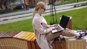 Muchacha que trabaja en el ordenador portátil como sentarse en el banco almacen de metraje de vídeo