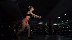 Muchacha que trabaja en el simulador Muchacha hermosa con el tríceps permanente de las sacudidas metrajes