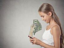 Muchacha que trabaja en línea en el dinero de la ganancia del smartphone Imagenes de archivo