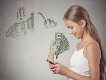 Muchacha que trabaja en línea en el teléfono elegante que hace el dinero de la ganancia Fotografía de archivo