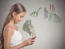 Muchacha que trabaja en línea en el teléfono elegante que hace el dinero de la ganancia Imágenes de archivo libres de regalías