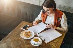 Muchacha que trabaja en línea, estudiante que hace la preparación En la taza de la tabla de té, galletas, smartphone Aprendizaje  fotografía de archivo libre de regalías