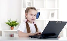 Muchacha que trabaja en la computadora portátil Fotos de archivo