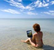 Muchacha que trabaja en la computadora portátil en el mar Foto de archivo libre de regalías