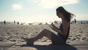 Muchacha que trabaja en la playa con PC de la tableta almacen de metraje de vídeo