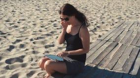 Muchacha que trabaja en la playa con PC de la tableta metrajes