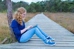 Muchacha que trabaja en la tableta en la trayectoria en naturaleza Imágenes de archivo libres de regalías